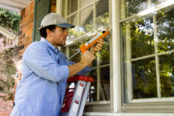 man fixing home windows exterior