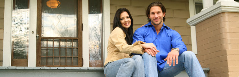 couple sitting on front porch of home